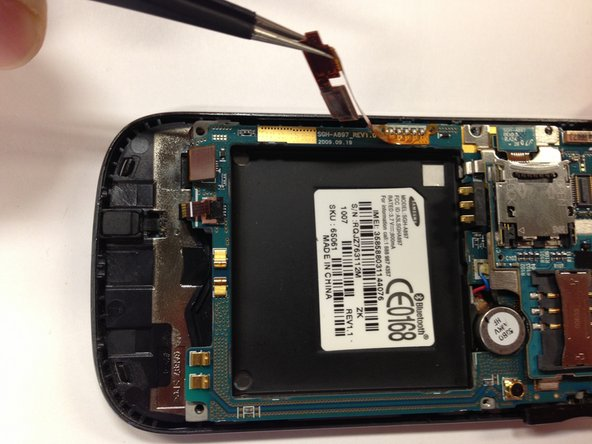 Use the tweezers to unclip the orange flexible circuit board from the side of the phone.