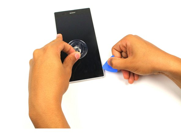 Image 2/2: While pulling on the small suction cup, slide the pick between the screen and the casing in order to remove the LCD screen from the casing.
