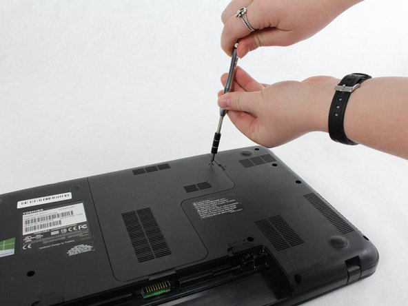 This screw does not come completely out, but you will still be able to get the panel off.