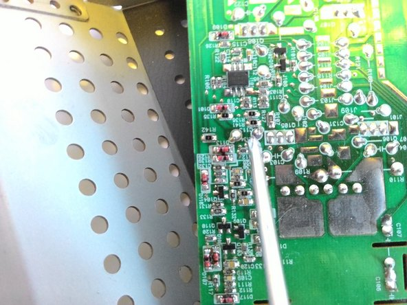 Image 2/3: Using a soldering iron and desoldering tape, remove the solder attaching any blown capacitors.