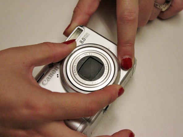 Image 2/2: While still pressing down on the button, grip the edges of the zoom lens ring and turn counterclockwise.