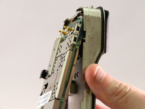 Image 1/3: The antenna jack, volume dial, and channel dial are attached to the motherboard. Be sure to pull the motherboard downward so they clear their respective slots in the case.