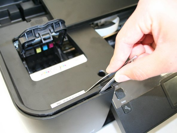 Remove the plastic cover by unlocking the plastic hinges at the inside edges of the printer. Use a plastic opening tool or a tweezer to slowly move in between the crease around the printer to unlock it.