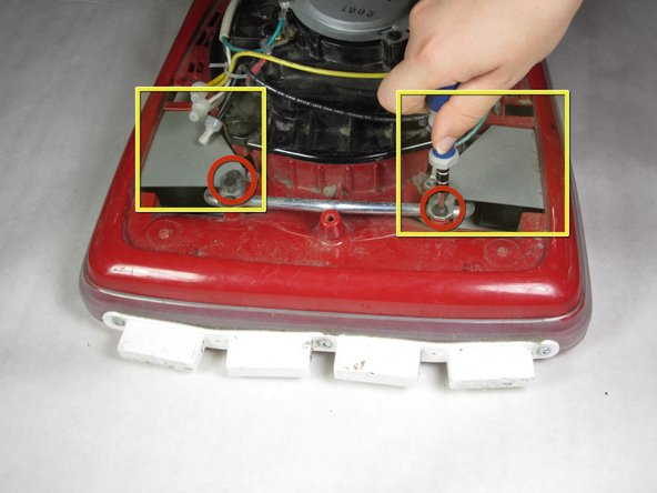 Identify the two gray metal plates at the front of the vacuum.