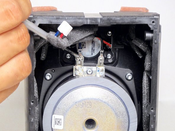 Using a metal spudger, press the release located in the center of the connector .