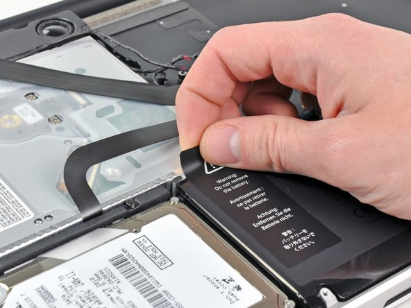Carefully peel the battery warning label off the upper case between the battery and the optical drive.