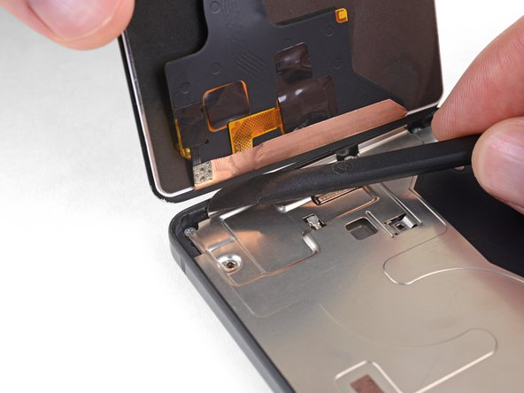 Use your halberd spudger to carefully separate any remaining adhesive along the bottom edge of the phone.
