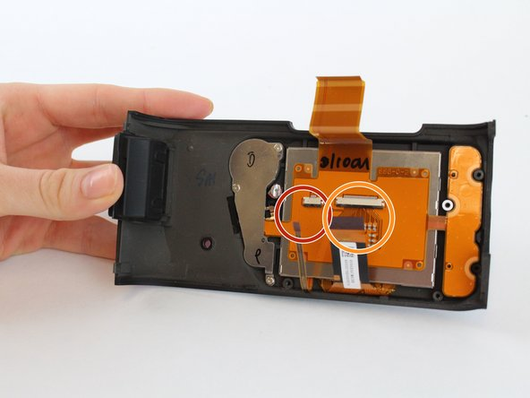 Use blunt tweezers to pull the left ribbon connector out of the zero insertion force connector.