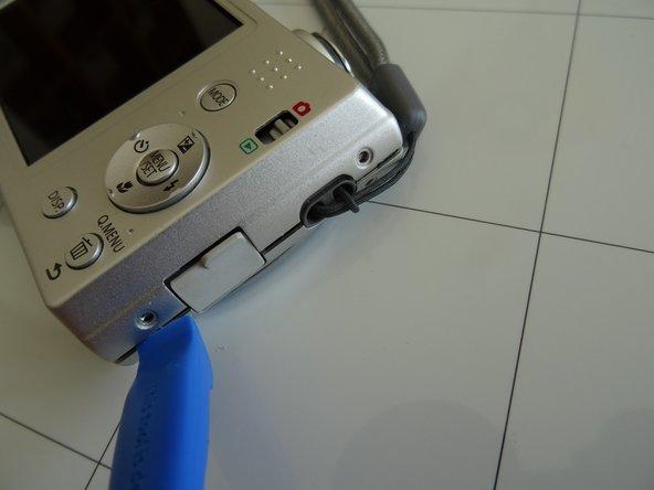 Löse den hinteren Gehäusedeckel mit einem Spudger oder einem Plastiköffnungswerkzeug ab. Fange neben der USB Abdeckung an und lasse das Werkzeug rings um die Kamera herum laufen. Hebe den hinteren Gehäusedeckel ab.