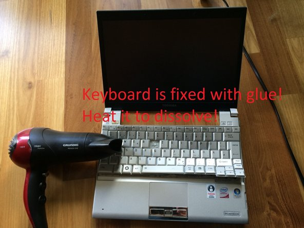 Heat the keyboard to loosen the adhesive.