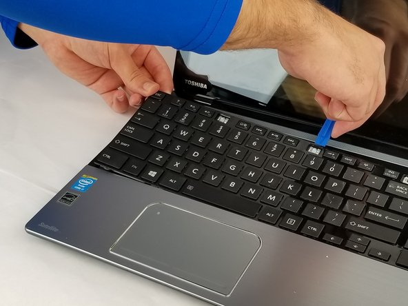 Using one of the plastic opening tools, gently run the tool along the gap between edge and the keyboard, prying it upwards.