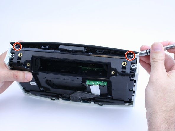Remove the two torx screws holding the speaker grill in place.