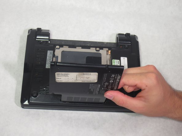 Using a plastic opening tool, take off the hard drive cover by lifting it up.