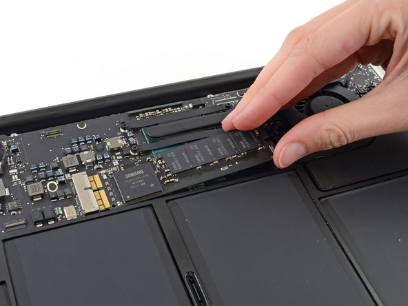 Don't lift the SSD more than half an inch—doing so may damage the SSD or its socket on the logic board.