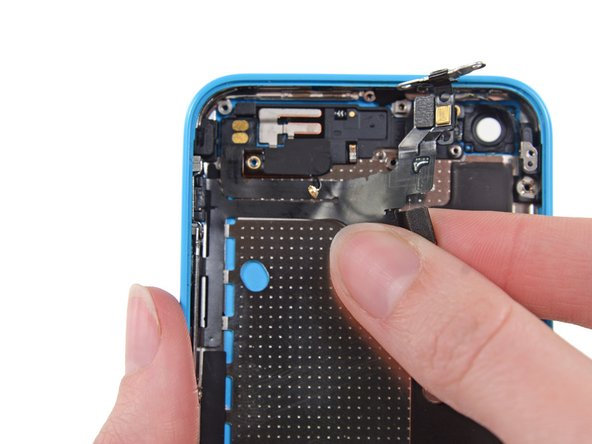 Image 1/2: Peel the upper assembly cable up from right to left to separate the adhesive holding it to the case.