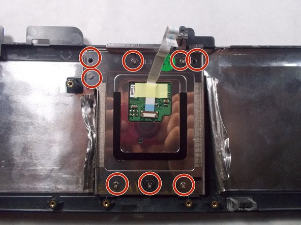 Locate the 8 points where the touchpad is fixed to the frame with screws.
