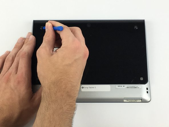 Image 1/2: Use a plastic opening tool to remove the two rubber grips on the back of the tablet.
