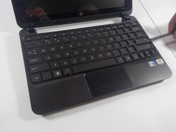 Using a prying tool, lift upwards and remove the plastic casing that covers the spaces around the keys of the keyboard.