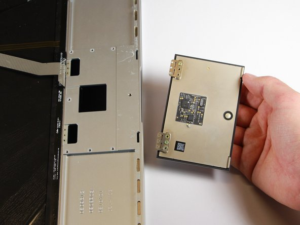 As the metal plates with the screws tilt upwards, use your hand to catch the falling touchpad and remove it.