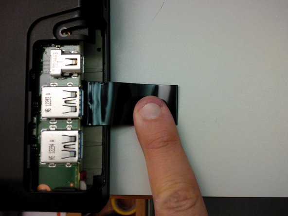 Insert a spudger (or a similar tool) under the loop of the black pull tab, and gently pull it out from above the hard drive.