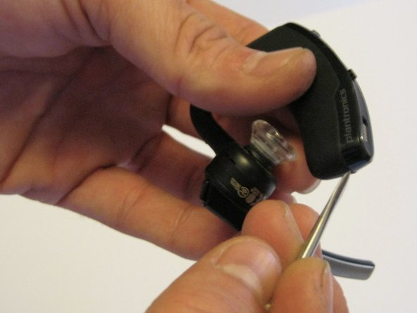 Use a heat gun (or a hair-dryer) to heat the main unit of the Plantronics Voyager Legend.  This will loosen the adhesive that bonds the covering to the housing.