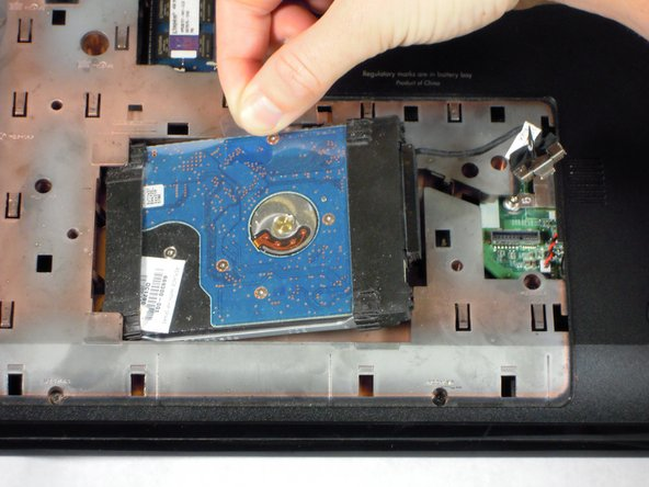 Image 1/2: Pull the hard drive up and to the right to remove it completely from the laptop.