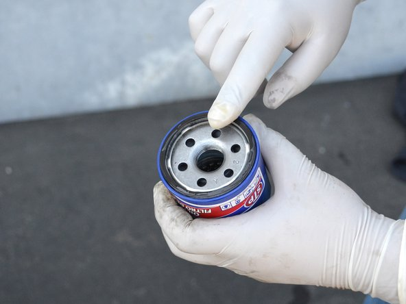 Spread the clean oil around the new oil filter's gasket.