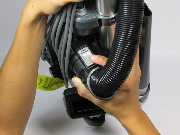 Locate the silver release levers on the top and bottom of the hose.