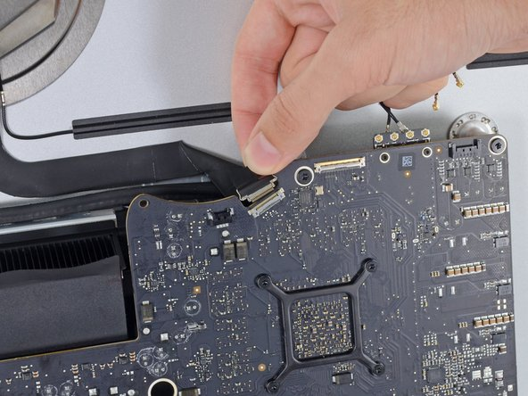 Image 3/3: Pull the camera cable connector straight out of its socket, toward the top of the iMac.