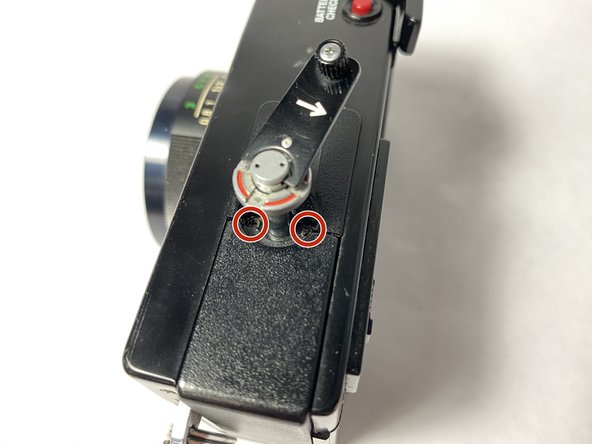 Raise the film crank to reveal the two screws under it.