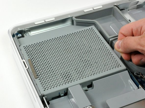 Pull the optical drive up by its white pull tab to disconnect it from the logic board.