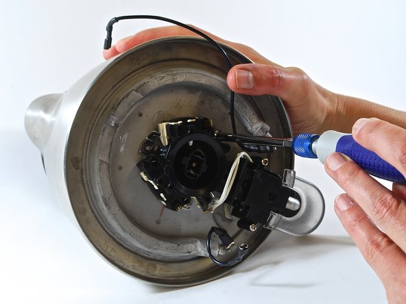 "FIRST IMAGE: Remove the power supply. Align the kettle as shown, with the handle to your right. Use the 7/32"" nut driver to remove the 7/32"" nut from the stud that is located clockwise from where the power supply was attached."