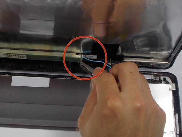 Image 2/2: Disconnect blue wire near the base of the screen with tweezers, by pulling it straight out