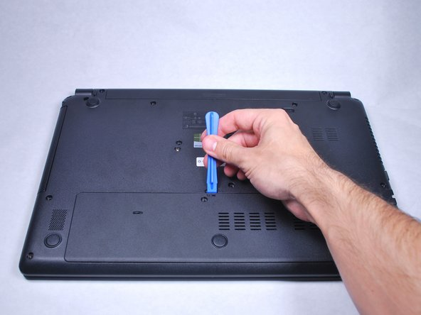 Use the plastic opening tool to pop off the small back cover.
