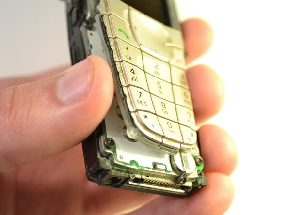 Image 1/2: Wipe off any excess dust from where the keypad was attached to the phone.