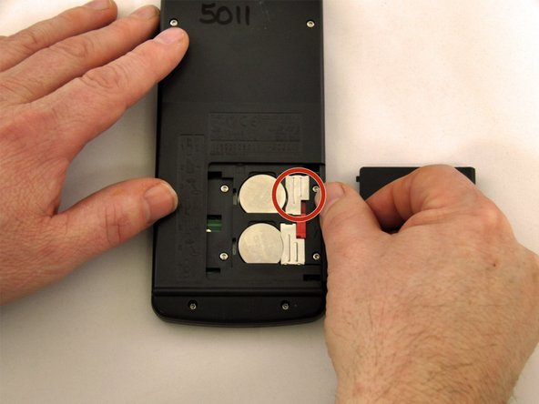 Slide the metal tab to the right of the bottom battery.