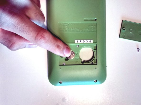 Image 2/2: Apply gentle pressure until the battery lays flush with the surrounding green housing.