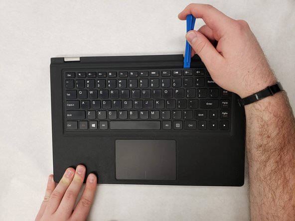 Use the blue opening tool to  further separate the keyboard bezel.