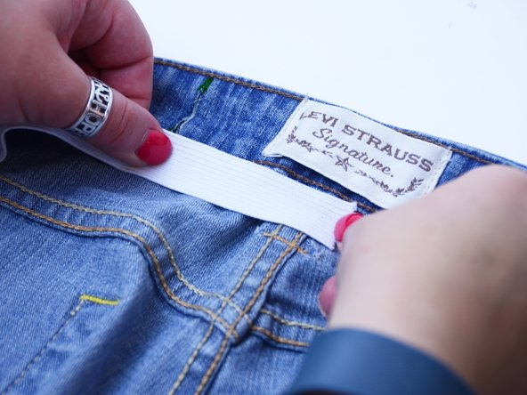 Measure and cut out a strip of elastic that is slightly smaller than the distance between the two cuts on the waistband.