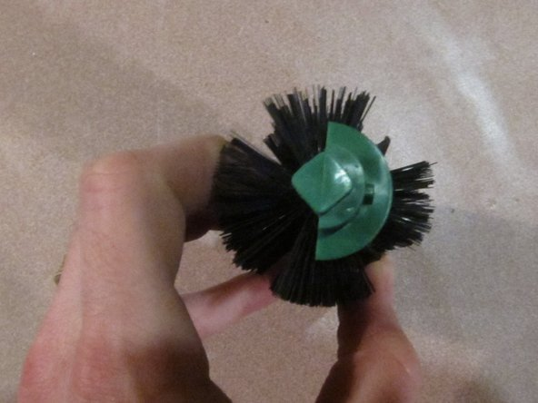Rotate the green brush housing so the line of bristles goes through the slot in the green brush housing.