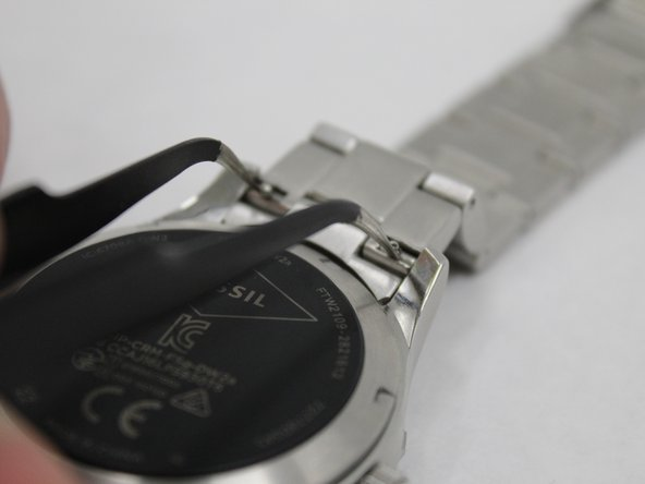 Squeeze retaining pins together to release chain from watch body. This can be done by hand or with tweezers.