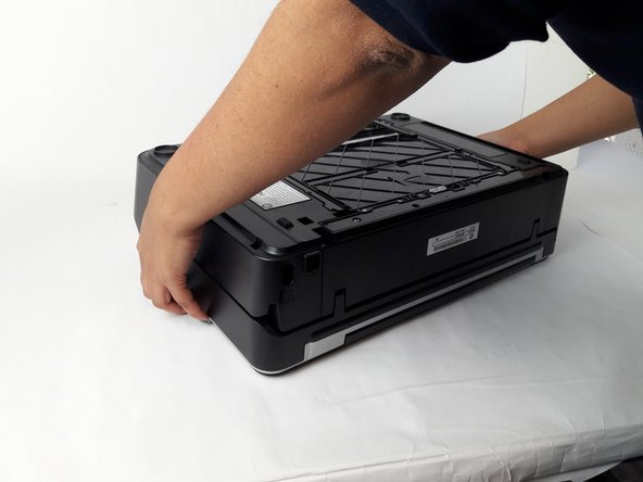 Grab both sides of the printer and flip it away from you so the bottom is facing up.