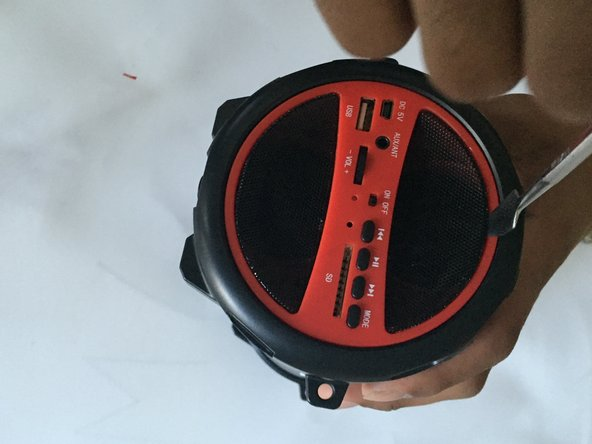 Use metal spudger to remove the mesh speaker covers (the side with the buttons) by wedging the narrow end into the center of the outer edge of the mesh, touching the red plate.