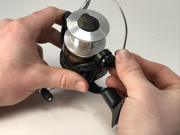 Slowly pull the base of the bail arm away from the reel in a twisting motion to separate the two parts.