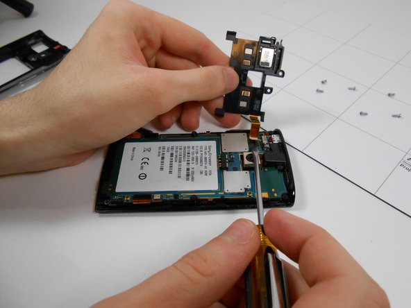 Flip the chip to the left and remove the ribbon cable from the rest of the phone using a flat head screw driver. Gently insert the screw driver under the cable and pry up.