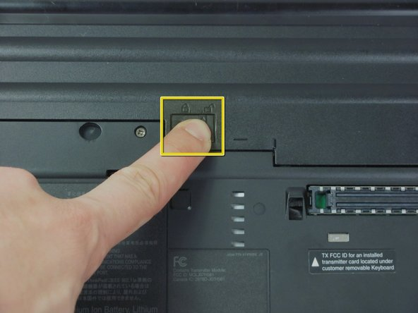 Image 1/1: Use your finger to slide the tab to the right to unlock the battery.
