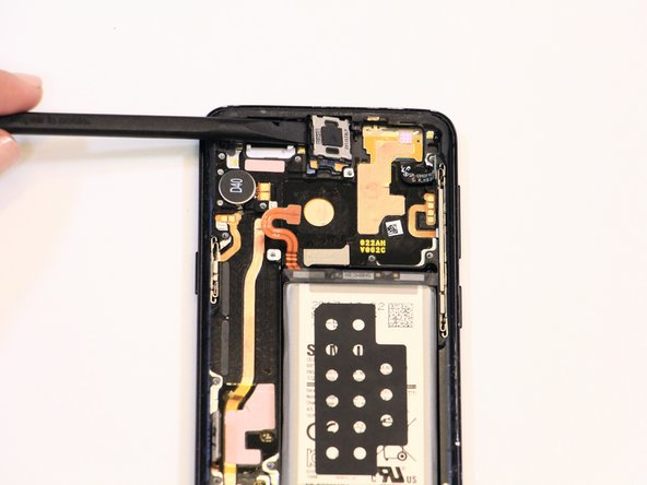 Remove the earpiece speaker by prying it off of the front display with the spudger.