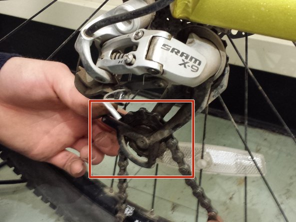 Image 1/3: Weave the chain thru the rear derailleur, make sure to guide the chain thru the rear chain guard.