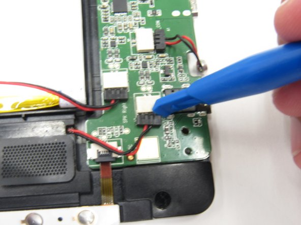 Wedge a plastic opening tool between the black and white modules on the circuit board to disconnect the wires of the speakers.