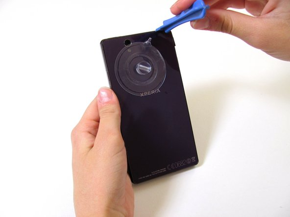 Once you've opened a small space with the back cover, stick the plastic opening tool into the seam of the phone.